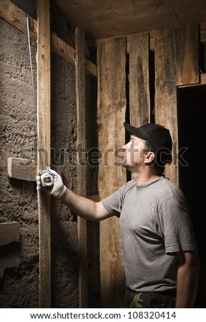 Builder measures the wall height of the tape