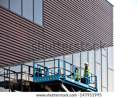 Builder on a Scissor Lift Platform at a construction site. Men at work