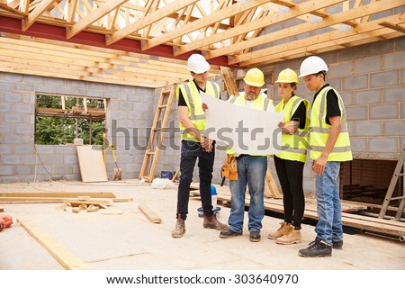 Builder On Building Site Looking At Plans With Apprentices