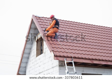 builder performs installation gable roof tiles of metal