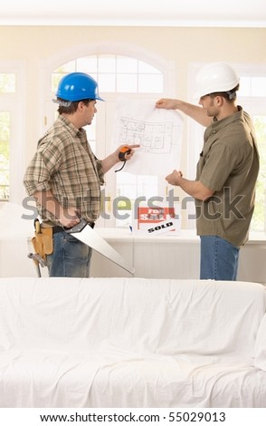 Builder pointing at ground plan, discussing project with architect.