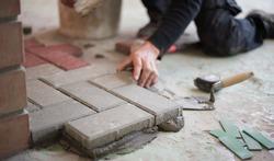 builder puts tiles in the yard. Paving slab. DIY home improvement.