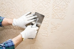 Builder repairman plasterer, applies decorative plaster, pattern on the wall, when repairing,