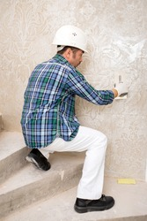Builder-repairman plasterer in a protective helmet while repairing applies decorative plaster, pattern on the wall, sitting