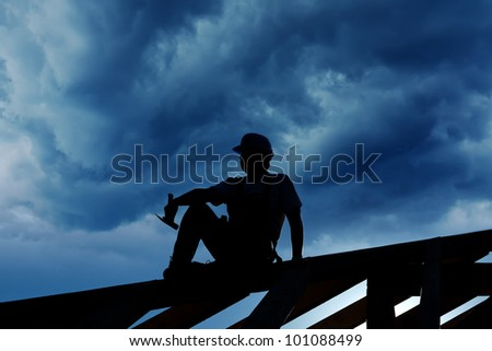 Builder resting on top of roof structure - silhouette against stormy sky