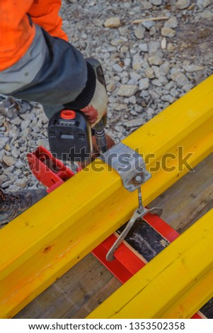 Builder's hands with a tool to connect metal beams and wooden beams #1353502358
