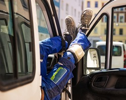 builder's legs in blue pants and work shoes on the door of a small truck on a sunny day
