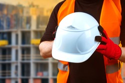 Builder shows a protective helmet. White helmet in hands of builder. Concept - protective clothing for construction workers. Man on background construction site. Concept - work a construction site.