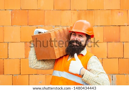 Builder shows thumb up. Labor protection at a construction site. Safety rules for builders. Happy builder in orange helmet holds brick against the background of the wall. #1480434443