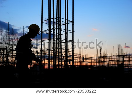 Builder Silhouette at Construction Site at Dusk