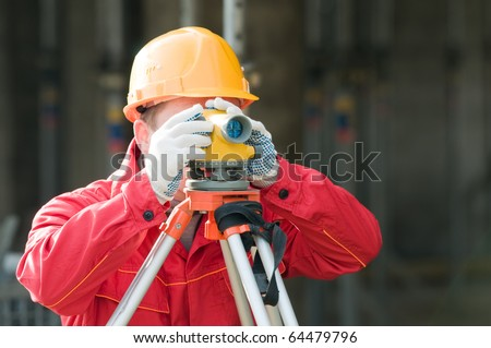 builder surveyor working with optical equipment level at construction site