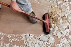 Builder sweeping the floor after renovation