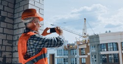 Builder taking photo with smartphone on construction site