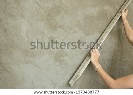 Mason using trowel plastering the concrete to build wall