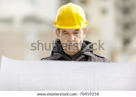 builder with blueprints on construction site