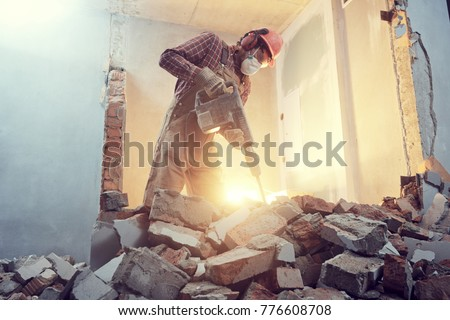 builder with hammer breaking wall indoors