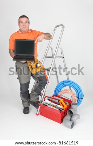 Builder with tools of the trade and a laptop computer