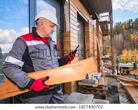Builder with wooden boards in his hands. Builder is calling someone. Concept - he orders lumber by phone. Purchase of lumber. A man in a builder's uniform. He outside a house under construction.