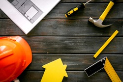 Builder work desk with hard hat, instruments and blueprints on dark wooden background top-down frame copy space