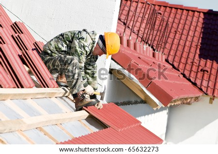 builder worker at roofing works on clay tiling with hammer screw nails