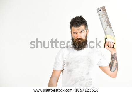 Builder, worker, carpenter, handyman holds saw, hacksaw, white background, copy space. Guy with beard covered with dust. Man on serious face in dirty shirt holds handsaw in hand. Brutal worker concept