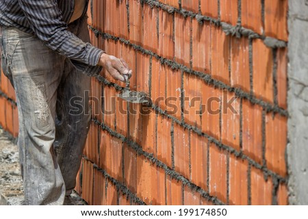 Builder worker, clay block wall and trowel. Builder worker using the sharp end of the trowel, scrape off any excess mortar that spreads beyond the joint. Selective focus and motion blur.