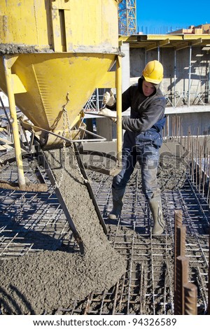 builder worker in hard helmet and uniform during concrete pouring works at construction site