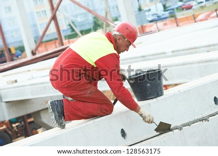 builder worker in safety protective equipment putting cement mortar on concrete floor slab panel at building construction site