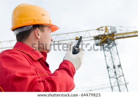 builder worker in uniform and helmet operating with tower crane by portable radio station transmitter
