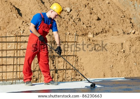 builder worker in uniform covering roof with insulation tar material at construction site