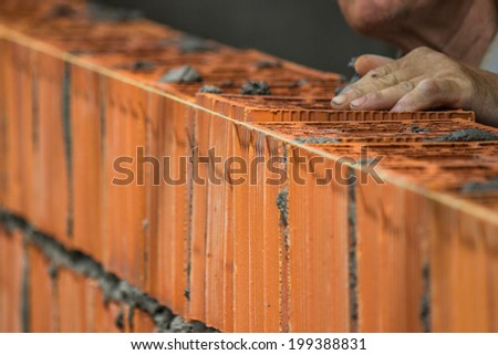 Builder worker installing clay block wall, lay clay block. Selective focus and motion blur.