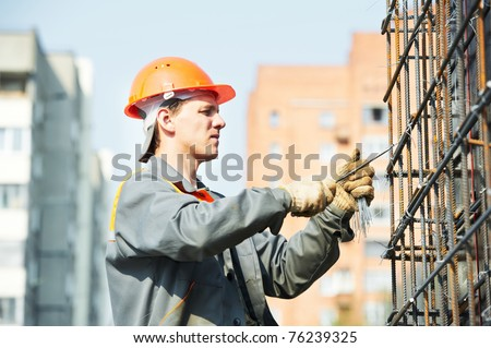 builder worker knitting metal rods bars into framework reinforcement for concrete pouring at construction site #76239325