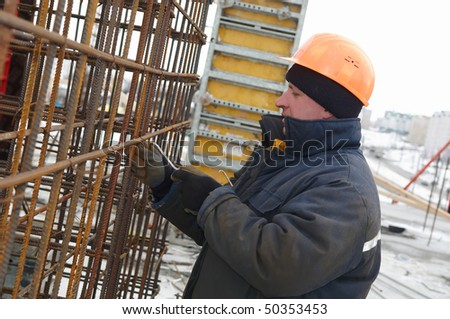 Builder worker making reinforcement metal framework lattice for concrete pouring