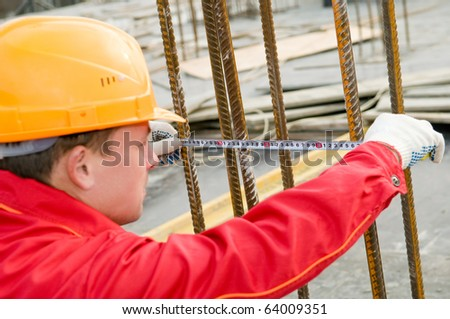 Builder worker measure the distance between reinforcement bars at construction site