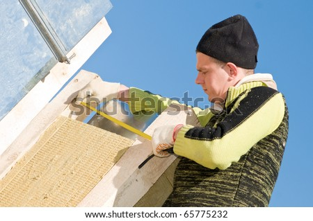 Builder worker measure the distance between timber planking roofing works at construction site