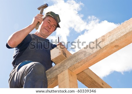builder worker nailing with hammer at roofing construction works