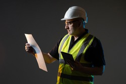 Builder worker on a dark background. Builder worker holding a tablet. Adult male architect. Architect in a reflective vest. Builder worker holds construction drawings. Experienced engineer architect