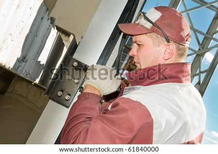 Builder worker tightening the screws at construction site with wrench