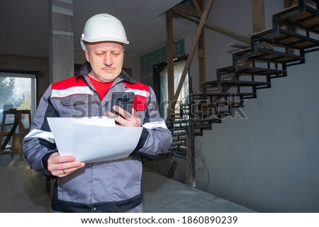 Builder worker with a phone in hand. Builder worker in a gray uniform. Construction worker talking by video link. He holds documents in his hands. Builder inside a house under construction.