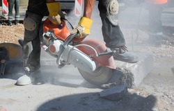Builder worker with cut-off machine power tool breaking concrete at road construction site