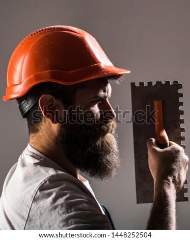 Builders in hard hat, helmet. Bearded man worker beard building helmet hard hat. Plastering tools. Tool, trowel, handyman, man builder. Mason tools, builder.