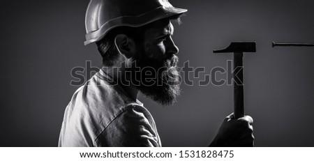 Builders in hard hat, helmet. Handyman, hammer, man builder, industry, technology, builder concept. Hammer hammering a nail Black and white #1531828475