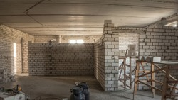Builders laying brick walls inside apartment with professional tools timelapse. Workmen at work, bricklayers building wall, contractor and worker. Building materials around