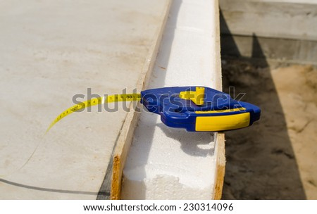 Builders tape measure on an insulating wall being installed in a new build house on a building site
