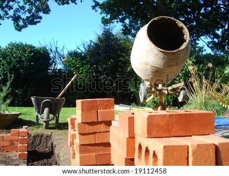Builders tools in garden. New conservatory being built.