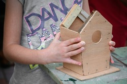 Building a birdhouse. Little Birdhouse in Spring. Plywood birdhouse on the table. Home made birdhouse. People hands. Family work. Wood work. Vintage birdhouse. Bird protect. Family work.