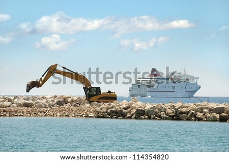 Building a dike. Excavator put stones in the sea. A ship on background