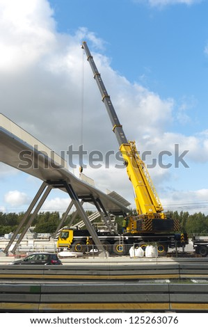 building a foot bridge over a busy road with a large construction crane