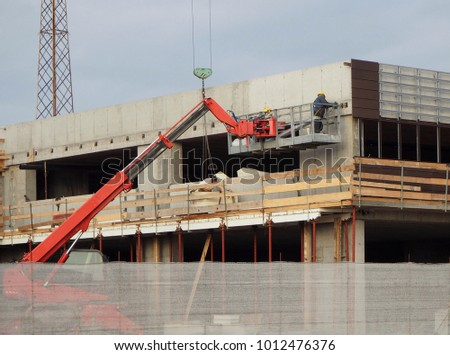 Building activity. Cherry picker at work on a facade of a new construction building