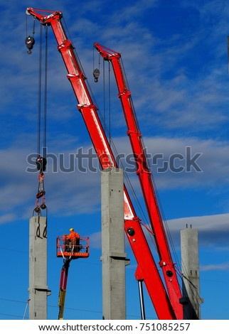 Building activity. Two telescopic cranes and a cherry pickers install the first concrete structural columns for a new construction